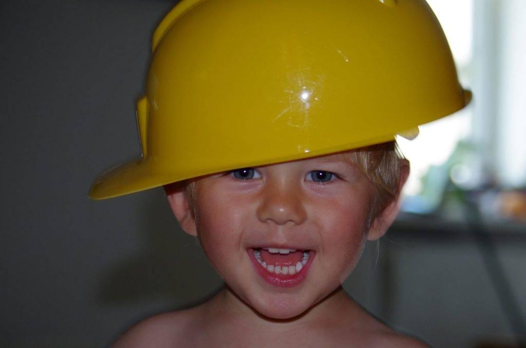 Ein kleiner Junge traegt einen gelben Sicherheitshelm quer auf dem Kopf.