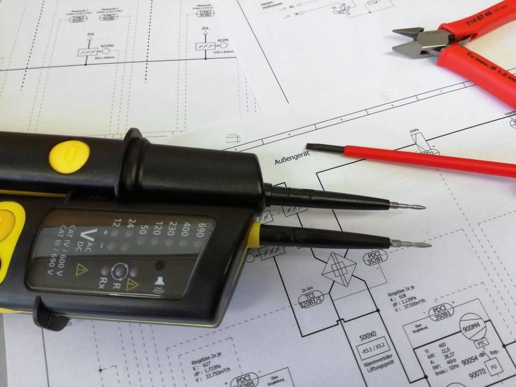 Ein Spannungsmessgeraet liegt auf einer technischen Zeichnung.